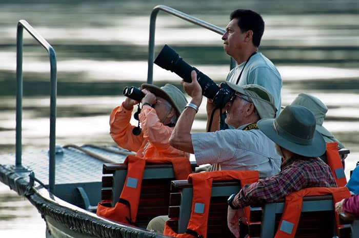 A guide with tourists during a boat excursion spotting wildlife with binoculars and a large camera lens in the Peruvian Amazon