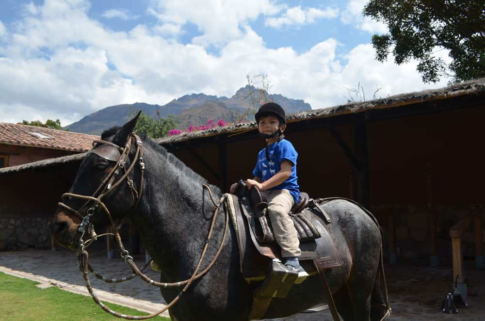 Six-year old boy doing horseback riding in the Sacred Valley of Cusco