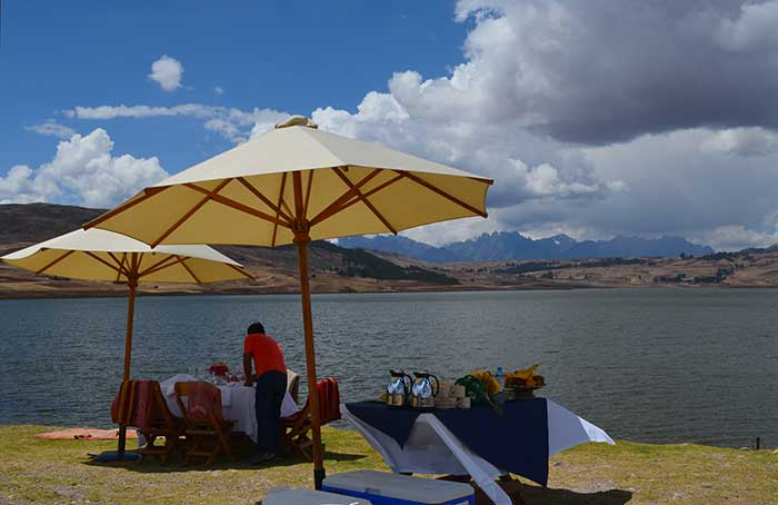 Man arranging a picnic at Huaypo Lake with views of the Andean Mountains
