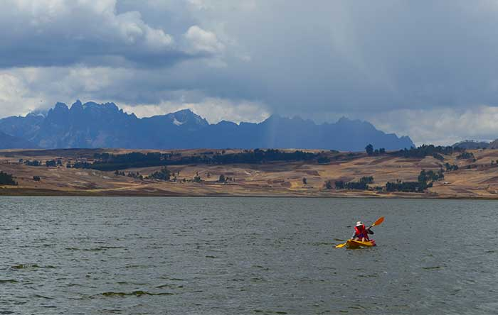 Traveler doing kayaking at the Huaypo Lake in the Sacred Valley of the Incas in Cusco with the Andean mountains as backdrop