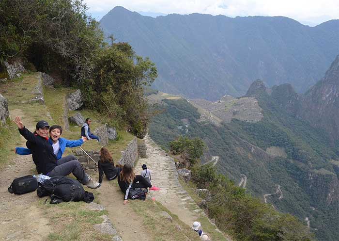 Machu Picchu With Kids, Mom & son sitting at Inti Punku (Sun Gate) with views of Machu Picchu
