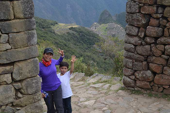 Machu Picchu With Kids A traveler with kid waving with Machu Picchu as background at Inti Punku Sun Gate