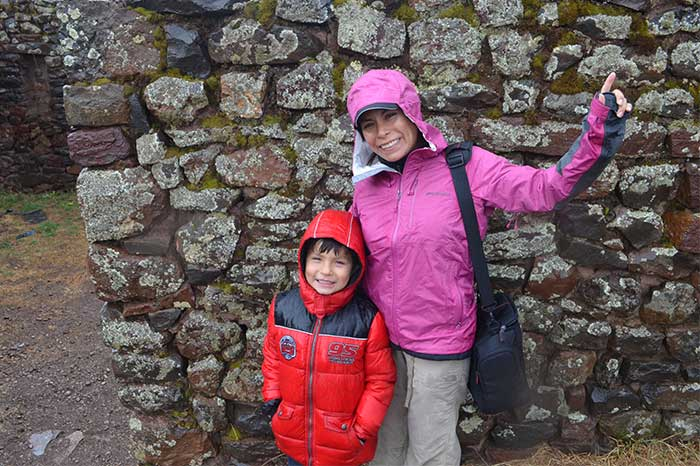 Machu Picchu with Kids, traveler with kid smiling at the camera having Pisaq ruins as backdrop