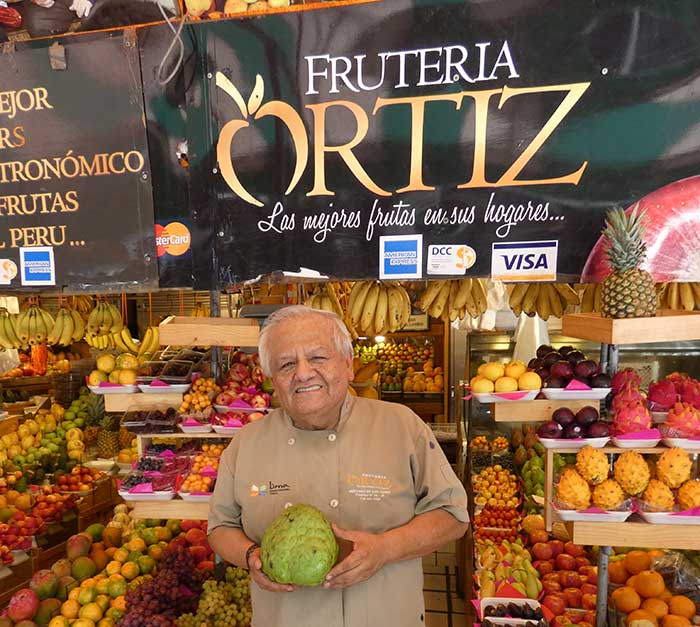 Mr Ortiz and his fruit stand in San Isidro's market - Lima, Peru