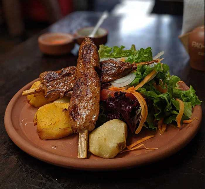Alpaca skewers served with potatoes and salad