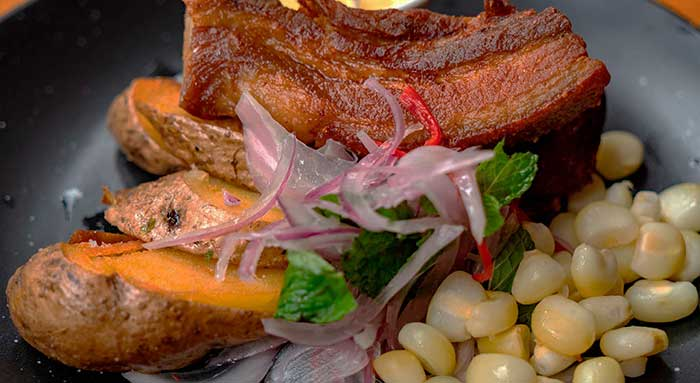 What to Eat in Cusco - Cusquenan-style fried pork belly served with maize, potatoes and onion salad