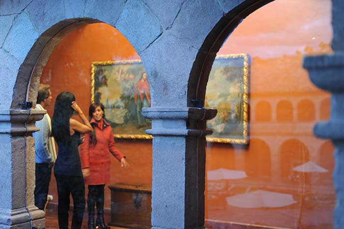 Guide at the Monasterio Hotel in Cusco explaining the colonial paintings to guests