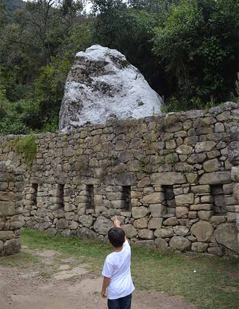 Visiting Machu Picchu with Kids - an Inca building and a sacred stone being shown by a kid