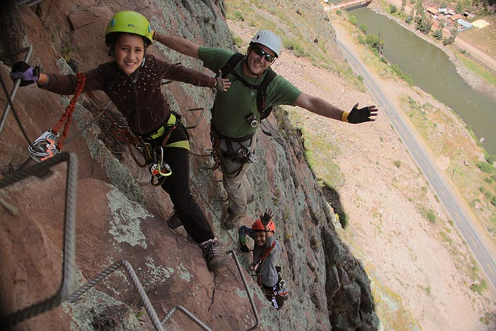 A kid & its father climbing up to the Skylodge using the via ferrata - Sacred Valley