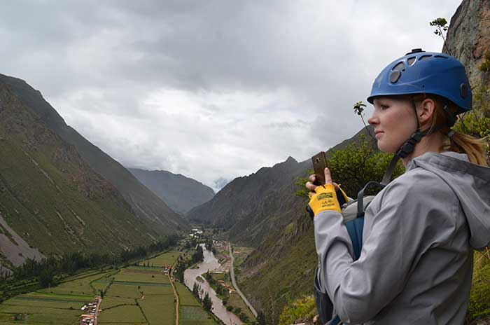 A tourist wearing climbing equipment watching over the Sacred Valley, after having reached the Skylodge
