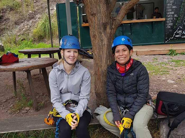 2 female guests wearing the equipment of Skylodge before climbing up to the pods, Sacred Valley, Peru
