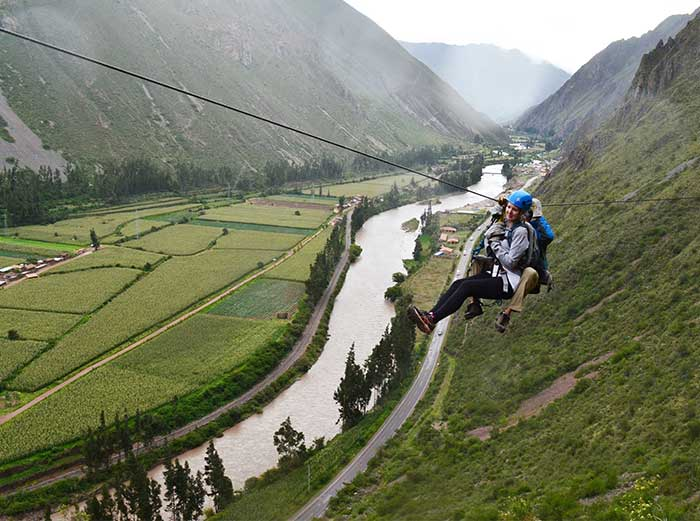 A tourist with a guide ziplining down to the Sacred Valley - Skylodge Peru