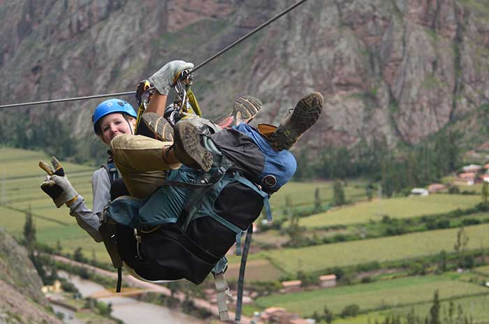 A tourist ziplining down with a guide from Skylodge Peru to the Sacred Valley