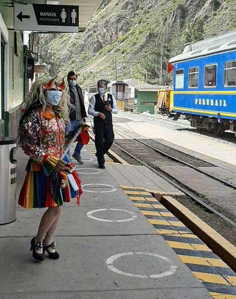 Machu Picchu New Rules 2021 -Lady wearing a mask and a colorful, traditional attire waiting in Ollanta train station to Machu Picchu